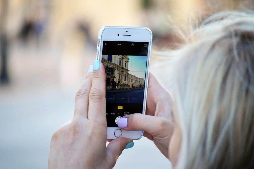 Frau macht ein Bild mit der iPhone Kamera