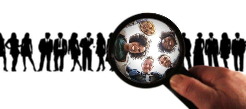 Zielgruppe definieren, schwarze Figuren im Hintergrund, Lupe die Menschen zeigt