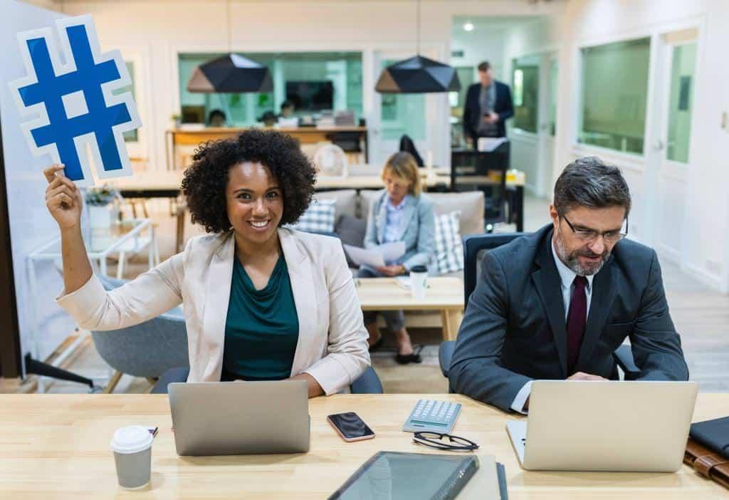 Schwarze Frau hält Hashtag Zeichen hoch, Mann neben ihr arbeitet am Laptop