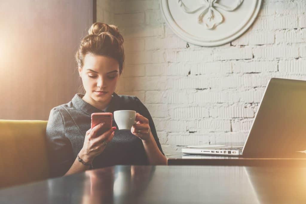 Frau sitzt mit Kaffee und Smartphone am Tisch