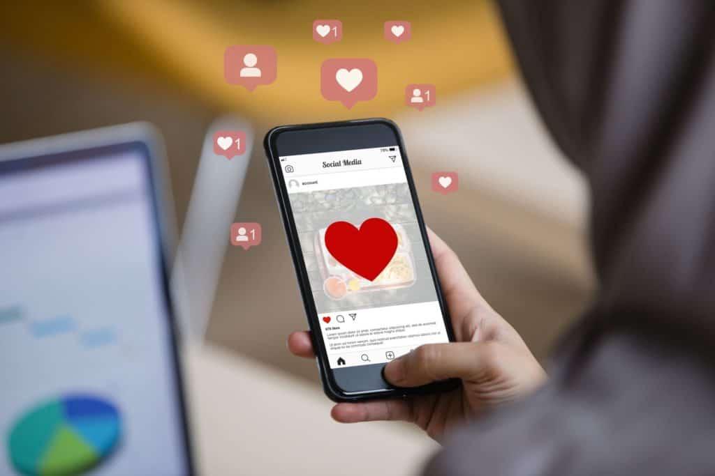 Frau tippt auf Smartphone und sieht ein großes, rotes Herz in der Instagram App