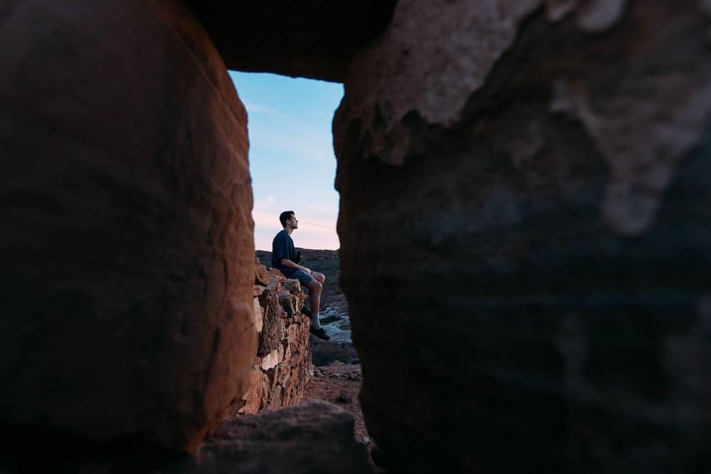 Durch das Schlüsselloch schauen, Mann sitzt auf einer Mauer
