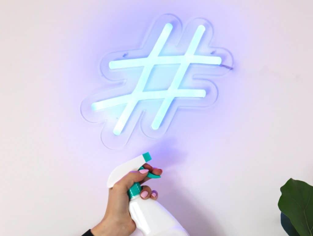 Person reinigt leuchtendes Hashtag Zeichen,